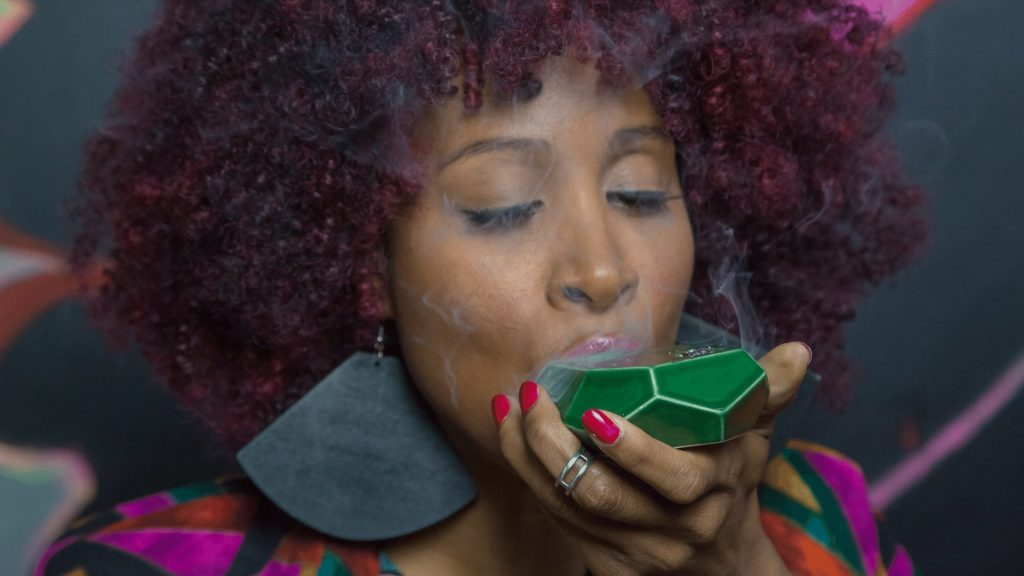 black woman curly afro smoking weed out of a bowl